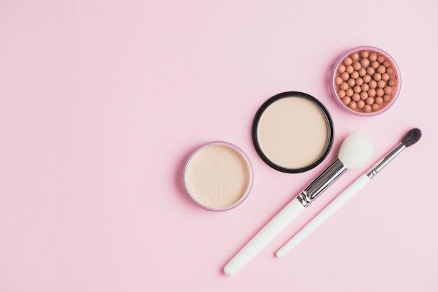 Vue aérienne des poudres pour le visage; perles de bronzage et pinceaux de maquillage sur fond rose Photo gratuit