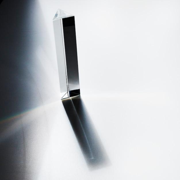 Vue aérienne d'un prisme en quartz avec une ombre sombre sur fond blanc Photo gratuit