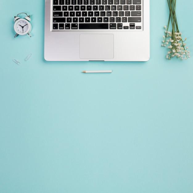Une vue aérienne de réveil, crayon avec ordinateur portable et muguet sur le bureau bleu Photo gratuit