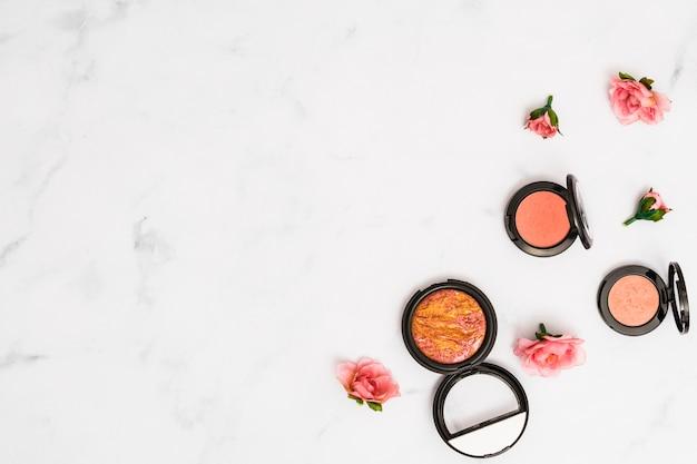 Vue aérienne, de, roses roses, à, compact, poudre visage, sur, blanc, texturé, toile de fond Photo gratuit