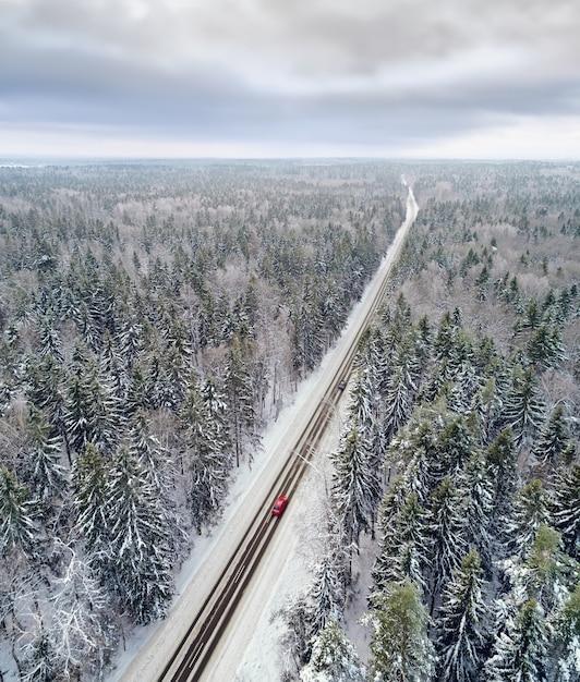 Vue Aérienne De La Route Couverte De Neige Dans La Forêt D'hiver Avec Des Voitures En Passant Photo Premium