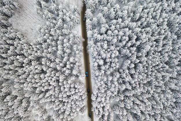 Vue Aérienne De La Route Avec Des Voitures Dans La Forêt D'hiver Avec De Hauts Pins Ou épinettes Couvertes De Neige. Conduire En Hiver. Photo Premium