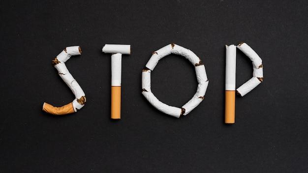 Vue aérienne d'un texte d'arrêt composé de cigarettes Photo gratuit