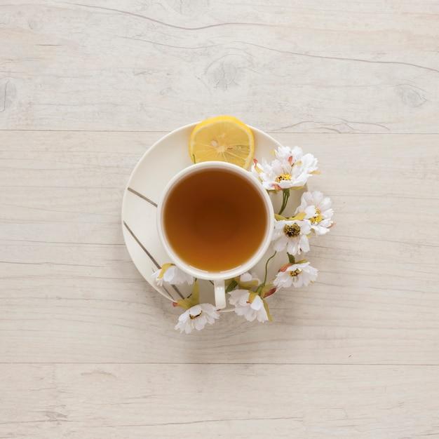 Vue Aérienne De Thé Au Citron Dans Une Tasse Avec Des Fleurs Et Citron Sur Une Soucoupe Photo gratuit