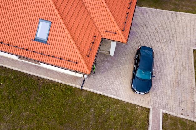 Vue Aérienne De Toit De Maison En Bardeaux Métalliques Avec Fenêtre De Grenier Et Voiture Noire Sur Cour Pavée. Photo Premium