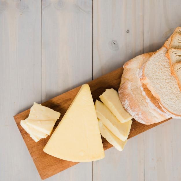 Une vue aérienne de tranches de pain avec des quartiers de fromage sur une planche à découper sur une table en bois Photo gratuit