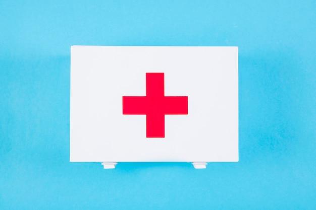 Vue aérienne de la trousse de premiers soins avec signe médical sur fond bleu Photo gratuit