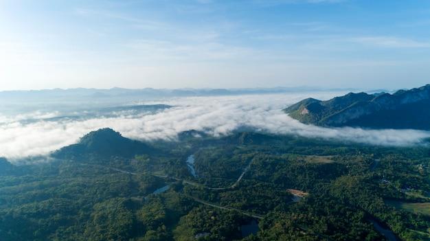 Vue aérienne des vagues de brouillard qui coule sur la forêt tropicale humide de montagne Photo Premium