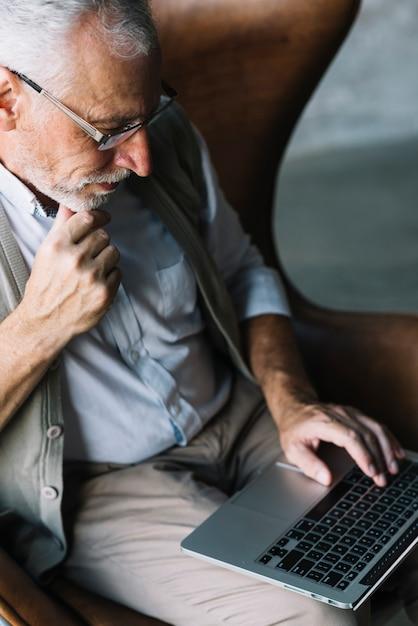 Vue aérienne d'un vieil homme assis sur une chaise à l'aide d'un ordinateur portable Photo gratuit