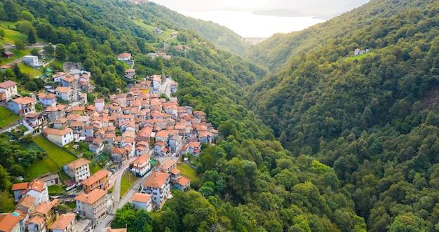 Vue Aérienne Sur Le Village Italien De Montagne, Garzeno. Portrait De Maisons Aux Toits Rouges Parmi Les Arbres Au Sommet De La Montagne En été. Photo Premium