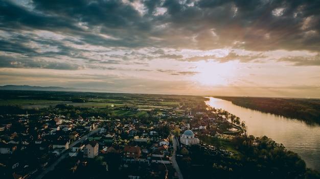 Vue Aérienne D'une Ville Près D'une Rivière Et De Champs Herbeux Sous Un Ciel Nuageux Photo gratuit