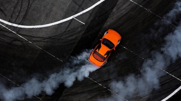 Vue aérienne de la voiture à la dérive sur la piste de course en asphalte avec beaucoup de fumée. Photo Premium