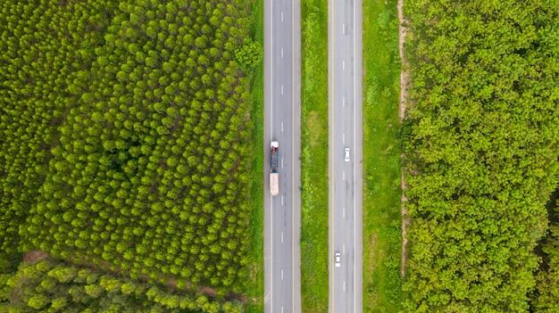 Vue aérienne de voitures et de camions sur la route goudronnée traverse la forêt verte Photo Premium