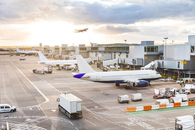 Vue de l'aéroport occupé avec des avions et des véhicules de service au coucher du soleil Photo Premium