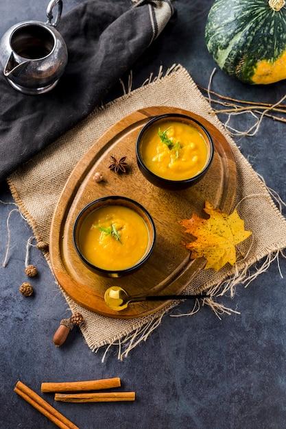 Vue d'angle élevé de bols de soupe à la courge sur planche de bois Photo gratuit