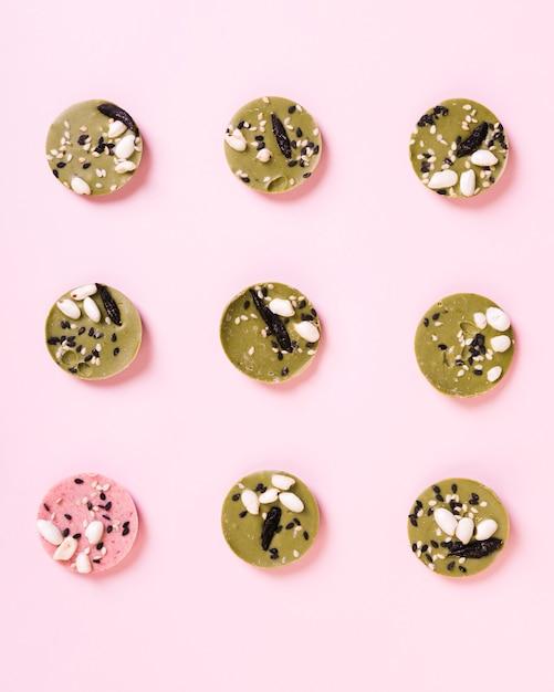 Vue d'angle élevé de dessert rond rose parmi les desserts verts disposés en rangée sur fond Photo gratuit