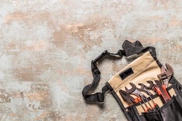 Vue d'angle élevé de divers outils dans le sac à outils sur le vieux fond en bois Photo gratuit