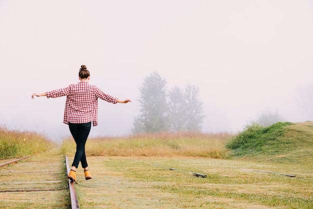 Vue arrière adolescente en équilibre à côté du chemin de fer Photo gratuit