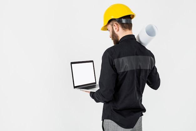 Vue arrière d'un architecte mâle regardant ordinateur portable sur le fond blanc Photo gratuit
