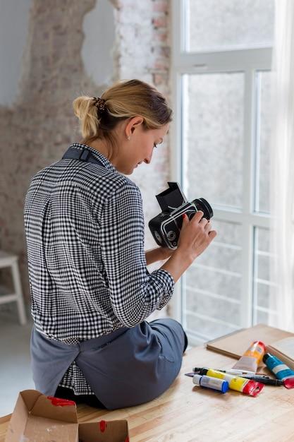 Vue arrière de l'artiste en tablier tenant l'appareil photo Photo gratuit