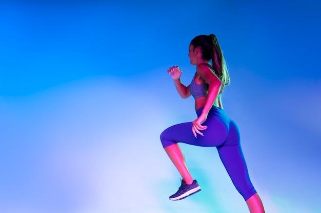 Vue arrière de l'athlète en cours d'exécution avec un fond bleu Photo gratuit