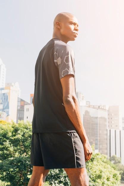 Vue arrière, de, athlète, homme musclé, debout, contre, bâtiments, dans ville Photo gratuit