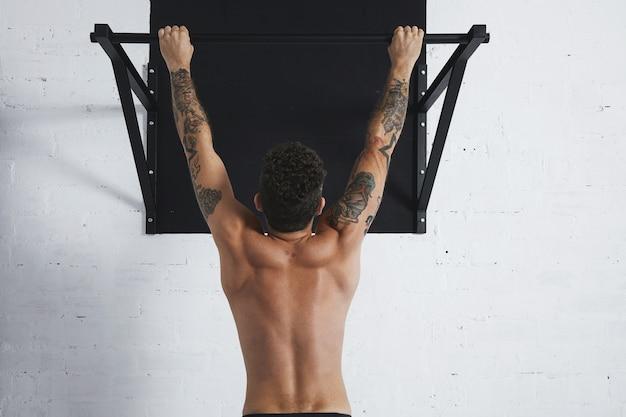 Vue Arrière Sur L'athlète Masculin Seins Nus Musclé Montrant Des Mouvements De Callisthénie Suspendu à Une Barre De Traction Photo gratuit