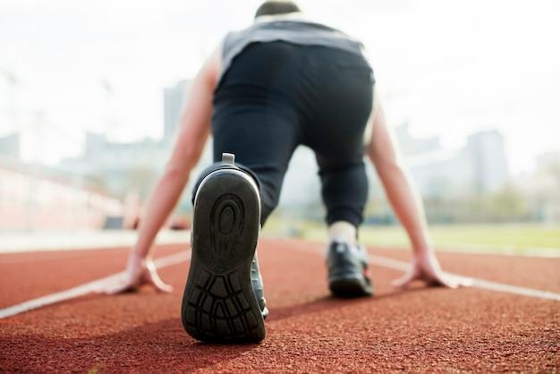 Vue arrière d'un athlète prenant position sur une piste de course rouge Photo gratuit