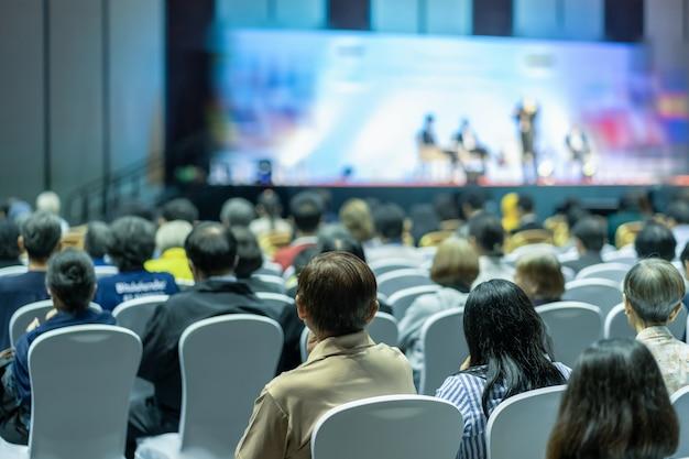 Vue arrière de l'audience à l'écoute des intervenants sur la scène dans la salle de conférence ou une réunion de séminaire Photo Premium