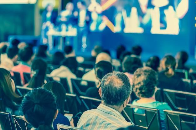 Vue arrière de l'audience à l'écoute des intervenants sur la scène dans la salle de conférence ou un séminaire moi Photo Premium