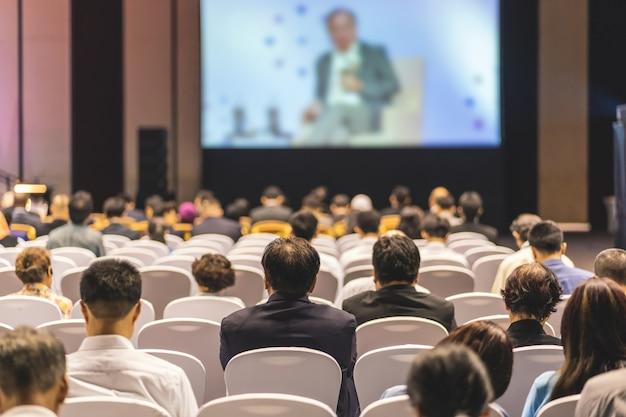 Vue arrière de l'audience à l'écoute des intervenants sur la scène dans la salle de conférence ou de séminaire Photo Premium