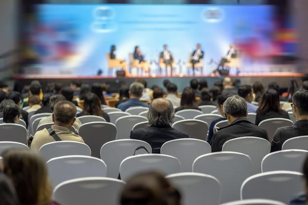 Vue arrière de l'auditoire à l'écoute des intervenants sur la scène dans la salle de conférence ou une réunion de séminaire Photo Premium