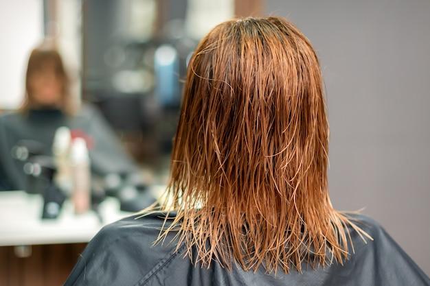 Vue Arrière De Beaux Longs Cheveux Raides Rouges Humides De Jeune Femme Dans Un Salon De Coiffure Photo Premium