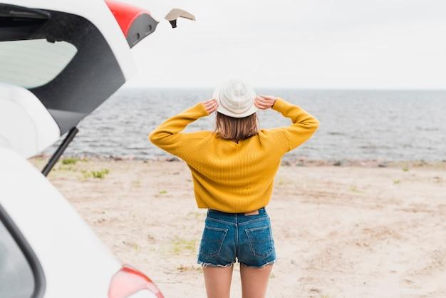 Vue arrière de la belle femme face à la mer Photo gratuit