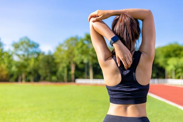 Vue arrière d'une belle jeune femme s'étirant au cours de son exercice du matin sur une piste de course à pied Photo Premium