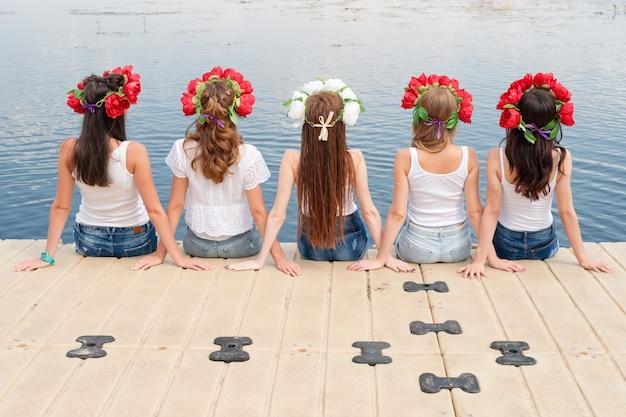 Vue Arrière De Cinq Jeunes Femmes, Portant Des Couronnes De Fleurs, Des Jeans Et Des T-shirts Blancs Photo Premium