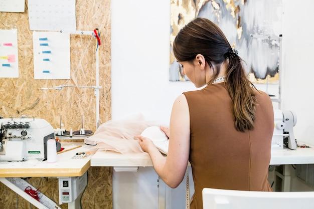 Vue arrière, de, a, concepteur femme, travailler, dans, magasin Photo gratuit