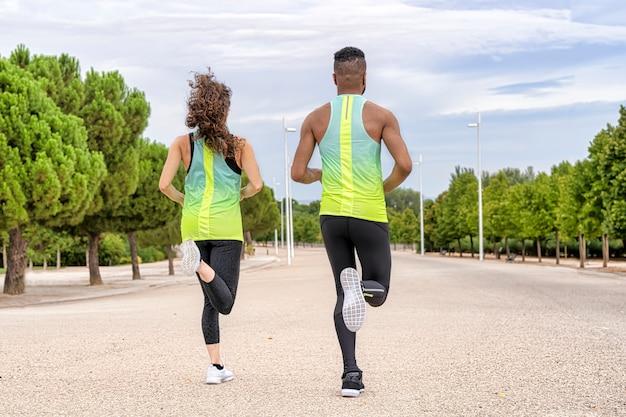 Vue arrière d'un couple de coureurs de différentes ethnies qui courent. l'homme est noir et la femme blanche Photo Premium