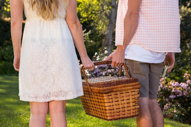Vue arrière d'un couple tenant un panier de pique-nique dans le jardin Photo Premium