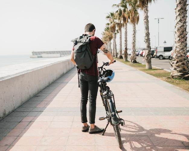 Vue arrière d'un cycliste debout à côté de la bicyclette Photo gratuit