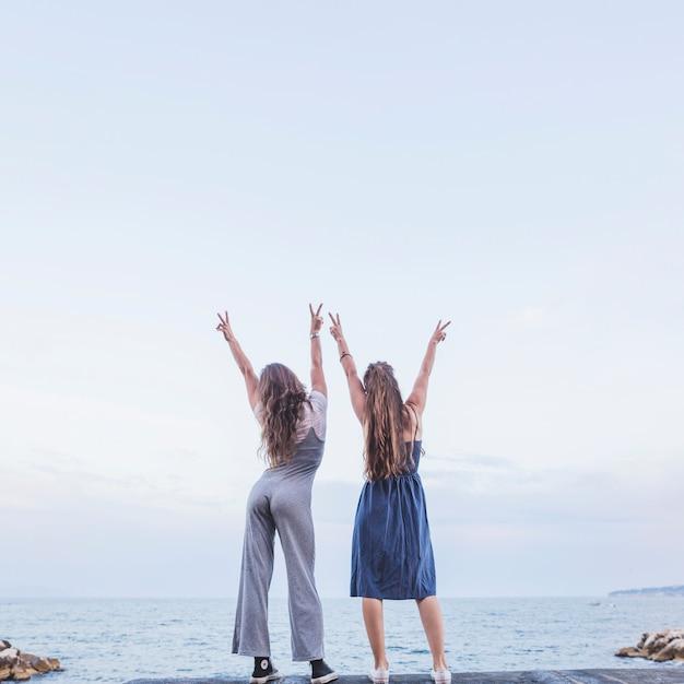 Vue arrière de deux amies debout sur la jetée en levant les mains montrant le signe de la paix Photo gratuit