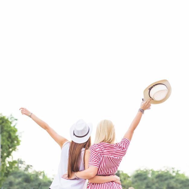 Vue arrière de deux amies levant la main Photo gratuit
