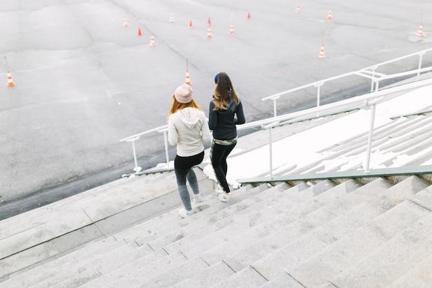 Vue arrière de deux femmes jogging sur l'escalier en hiver Photo gratuit