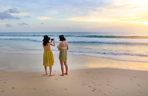 Vue arrière, de, deux femmes, photographié, les, beau, paysage, de, mer, coucher soleil, à, téléphone portable Photo Premium