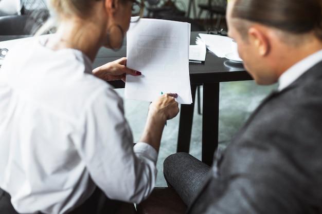 Vue Arrière De Deux Hommes D'affaires Examinant Un Document Dans Un Café Photo gratuit