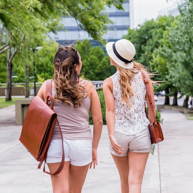 Vue arrière, de, deux, jeune femme, touriste, marcher rue Photo gratuit