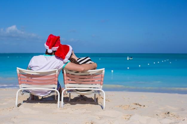 Vue arrière du couple en chapeaux santa profiter de vacances à la plage Photo Premium