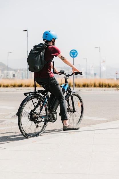 Vue arrière du cycliste en attente à l'arrêt Photo gratuit