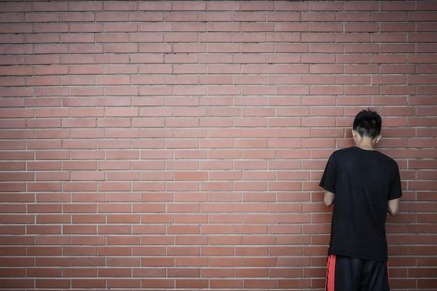 Vue arrière du garçon asiatique adolescent debout devant le fond de mur de briques rouges Photo Premium