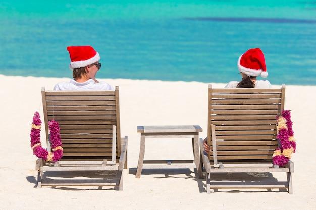Vue arrière du jeune couple en chapeaux santa se détendre sur une plage tropicale pendant les vacances de noël Photo Premium